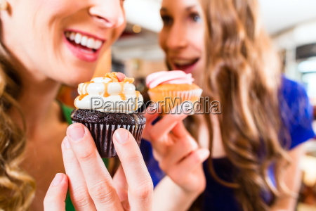 mujeres que comen panecillos beben el